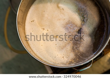 Froth of Home-Brew Mash in a Stock Pot While Sparging the water to Drain the Sugar - stock photo