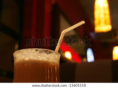 Froth on the cup of coffee in a clear glass (dark cafe background)