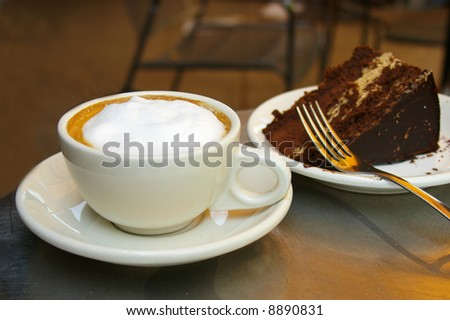 Frothy cappuccino coffee and chocolate cake