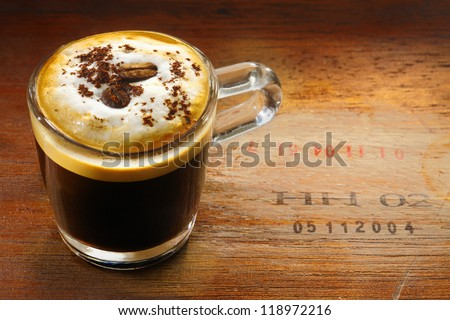 Frothy cup of espresso coffe or cappuccino topped with sprinkled chocolate and a single coffee bean on an old wooden surface stamped with numbers - stock photo