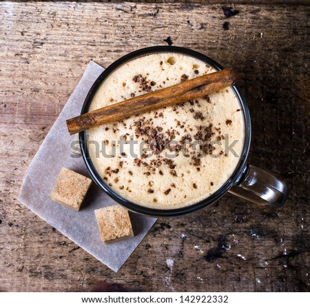 Frothy cup of espresso coffee with cinnamon topped with sprinkled chocolate on Old wooden background,   - stock photo