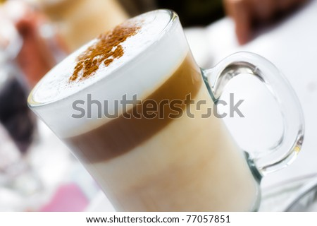Frothy, layered cappuccino in a clear glass mug with cinnamon sprinkled on top - stock photo