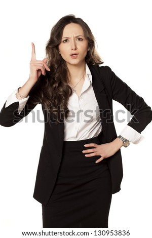 frowning and angry business woman pointing a finger upwards - stock photo