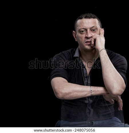 Frowning and thoughtful man sitting on a chair - stock photo