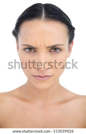 Frowning brunette posing in close up on white background - stock photo
