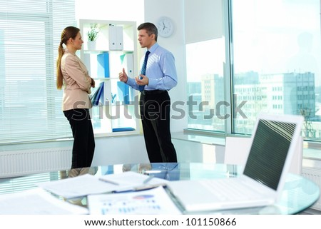 Frowning businessman explaining something to his female colleague - stock photo