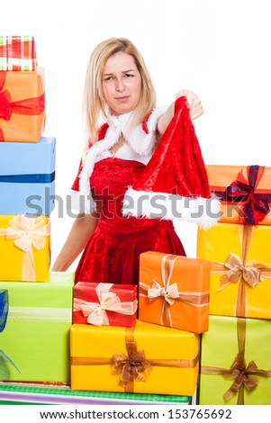 Frowning Christmas woman holding Santa hat, surrounded by presents, isolated on white background.