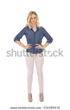 Frowning gorgeous blonde wearing classy clothes posing on white background - stock photo