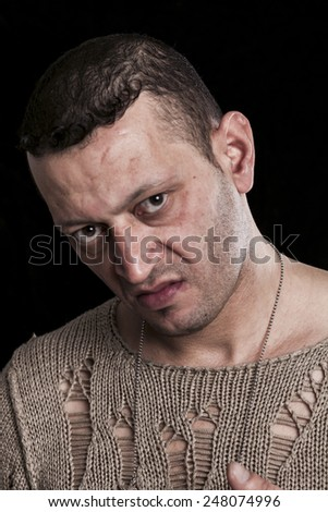 Frowning man portrait looking at camera on black closeup - stock photo