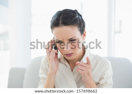 Frowning stylish brunette businesswoman making a phone call in bright office - stock photo