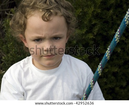 Frowning upset young boy with blue rope swing - stock photo