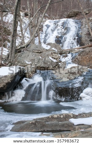 Frozen  and flowing waterfall in the woods