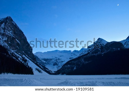 Frozen and snow covered Lake Louise, Alberta, late evening with new moon in the sky - stock photo