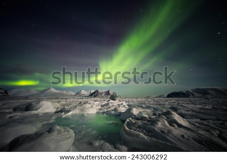 Frozen Arctic world with Northern Lights on the sky - stock photo