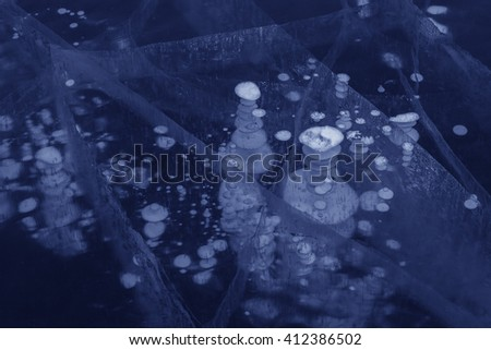 Frozen bubbles and cracks in the transparent ice. Beautiful winter landscape in the Lake Baikal. - stock photo