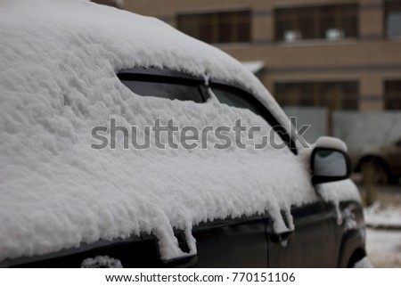 Frozen car covered snow at winter day