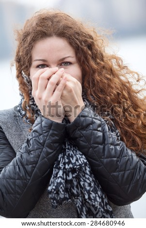 Frozen Caucasian woman with long curly hair blowing her hands while standing in cold weather - stock photo