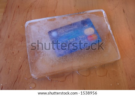 frozen credit card in a block of ice - stock photo