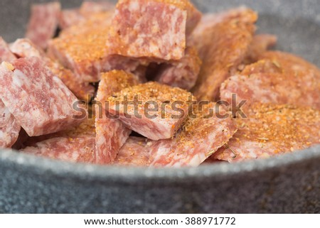 Frozen cut forcemeat with large pieces and sprinkled with spices on a grey ceramic frying pan in a kitchen - stock photo