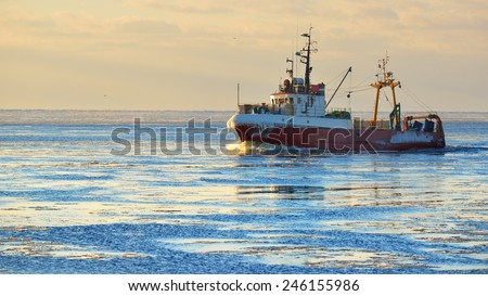 Frozen fishing vessel in coming back to the port at the sunset - stock photo