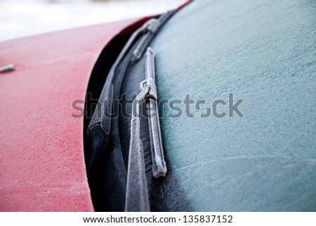 Frozen front windshield of car during winter morning