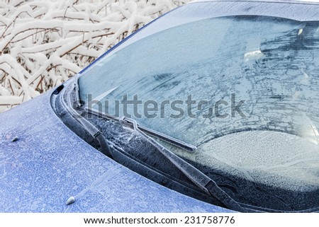 Frozen front windshield of car during winter morning - stock photo