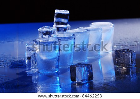 Frozen glasses and ice cubes with cold alcohol drink - stock photo