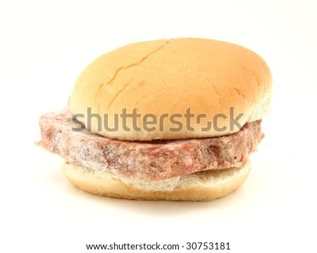 Frozen Hamburger Patty In Bun Isolated On White - stock photo