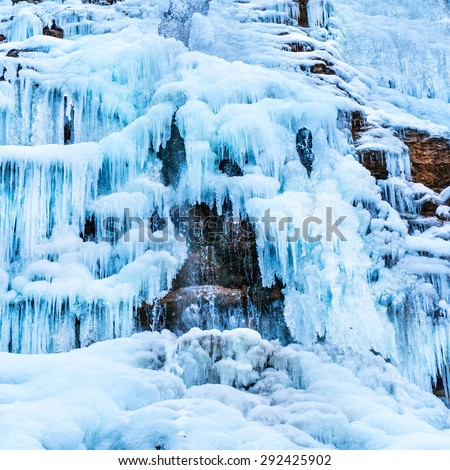 Frozen ice waterfall of blue icicles on the rock - stock photo