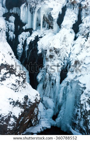 Frozen Icelandic waterfall with icicles and snow. Detail view of Hraunfossar waterfall. - stock photo