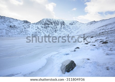 frozen lake in winter covered in snowy mountains, helvellyn, cumbria - stock photo