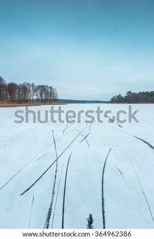 Frozen lake landscape. Beautiful lake in Poland with skate traces. - stock photo