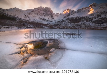 Frozen Lake Marvelous ice formations in a frozen lake surrounded by a magnificent mountain view near Nusfjord, in the beautiful Lofoten islands, Norway. - stock photo