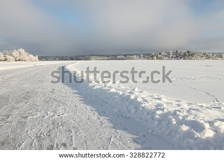 Frozen lake with ice road on it - stock photo