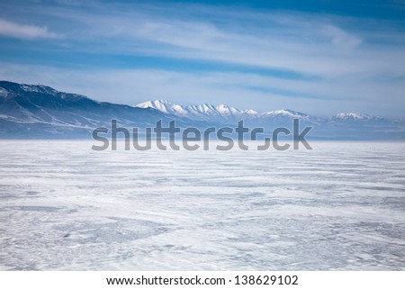 Frozen Lake with Mountains in the Background - stock photo
