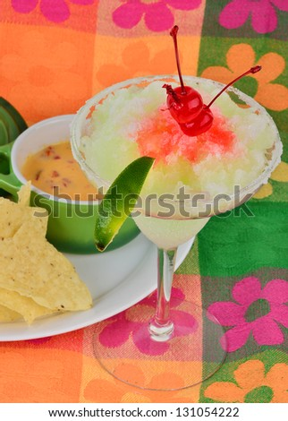 Frozen margarita with maraschino cherry and lime on brightly colored background served with chili con queso dip and tortilla chips. - stock photo