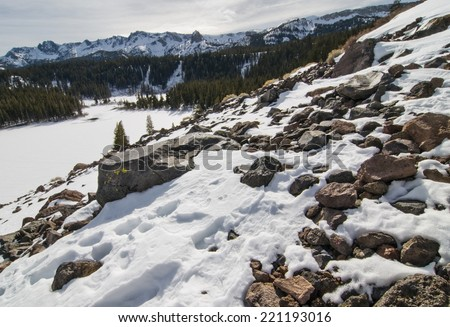 Frozen mountainside in Mammoth Lakes, CA overlooking frozen lake with Mammoth Rock in the distance