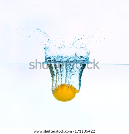 Frozen movement of lemon falling into water - stock photo