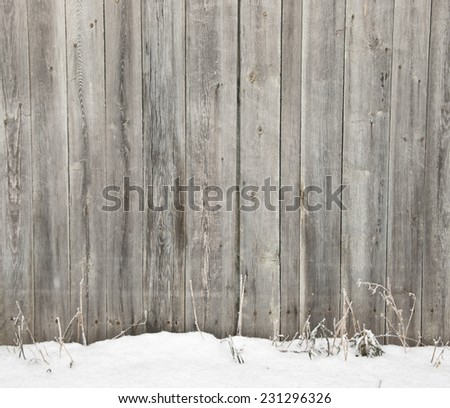 Frozen old wooden fence in snow  - stock photo