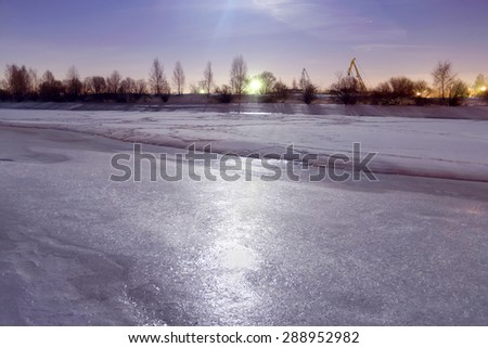 Frozen river covered with ice reflects light from moon at night - stock photo