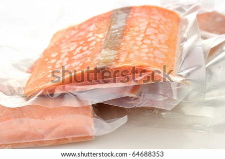 frozen salmon fillets in a vacuum package - stock photo