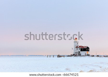 Frozen sea with lighthouse at sunset, Marken, the Netherlands - stock photo