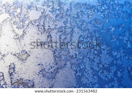 Frozen snowflakes and frost magic pattern with sunlight on Christmas winter window. Colored in gray or silver and blue tone. Selective focus with blur edges of image - stock photo