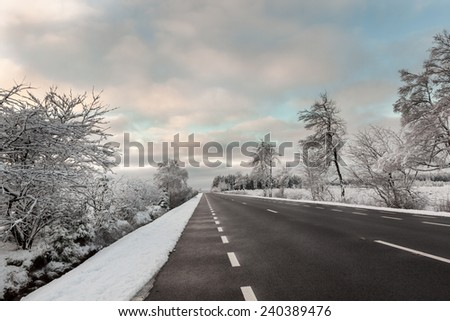 Frozen trees and snowy land road at winter