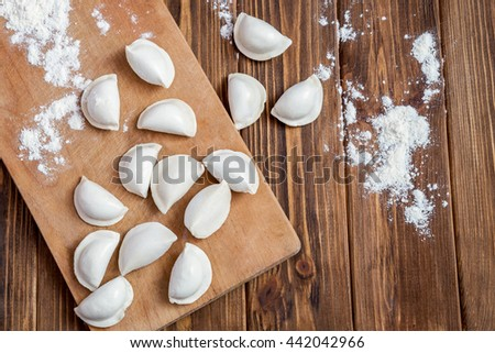 Frozen uncooked pierogi on wooden table. Top view - stock photo