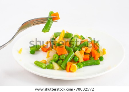 Frozen vegetables and fork on the plate - stock photo