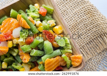 Frozen vegetables  in a wooden table. - stock photo