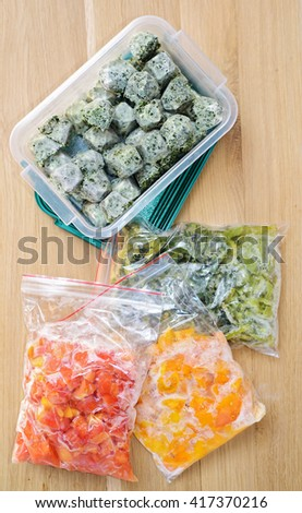 Frozen vegetables on cutting board and plastic bags. top view - stock photo