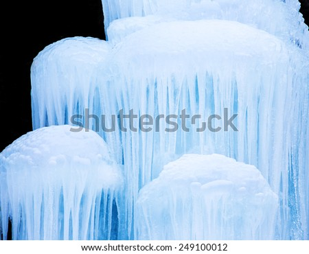 Frozen waterfall of blue icicles, close-up.