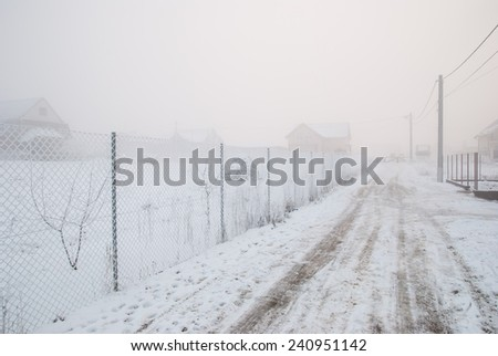 Frozen wire fence on a very cold and foggy winter day. Extreme cold weather conditions - stock photo
